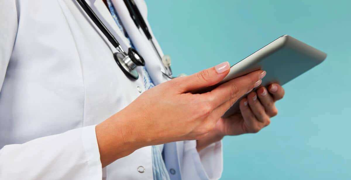 Close-up of female FNP holding a tablet device