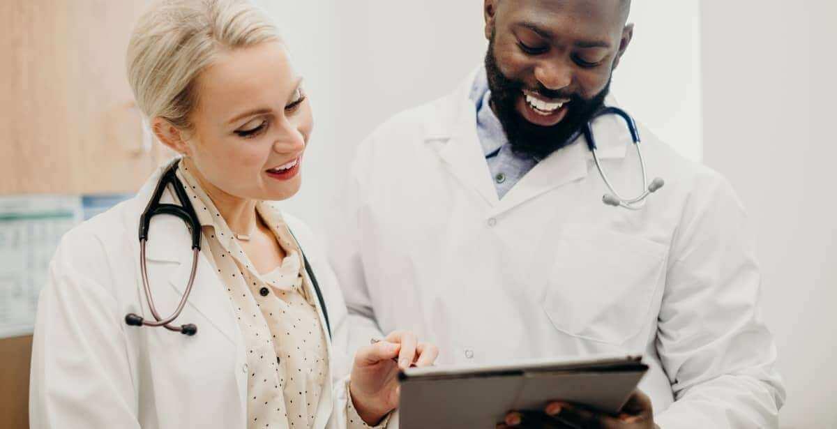 Male nurse and female nurse reviewing patient notes