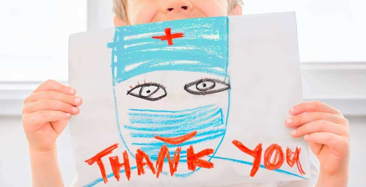 Child holding up thank you sign for nurses