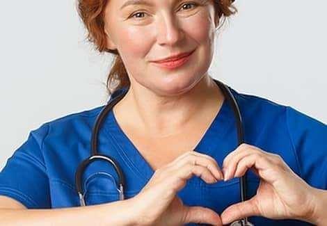 Nurse in blue scrubs holding hands in a heart shape